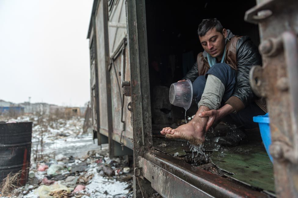 A man washes his foot in a shelter