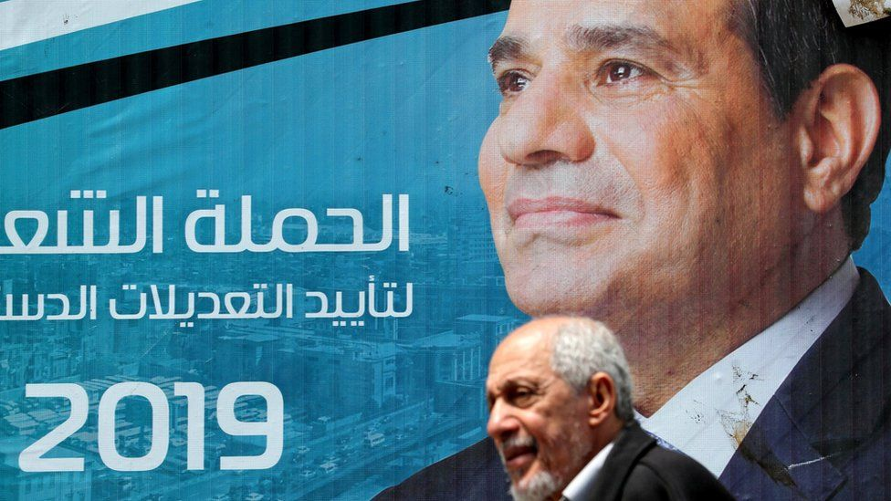 A man walks in front of a banner showing President Abdul Fattah al-Sisi and backing the proposed constitutional amendments in Cairo, Egypt (16 April 2019)
