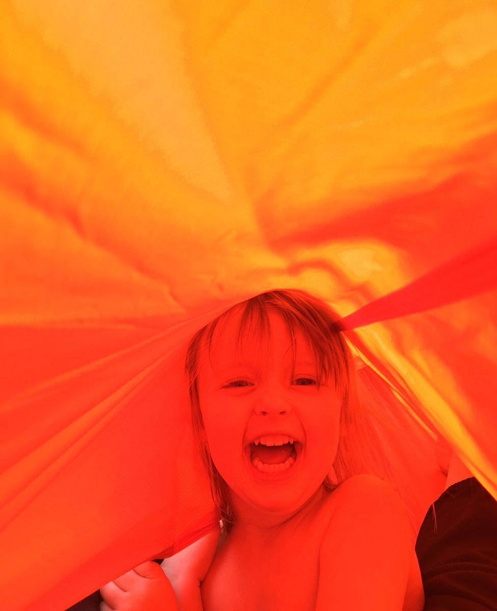 A child under a coloured cloth