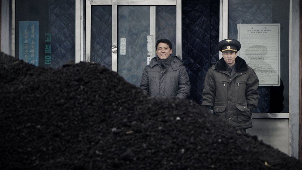This picture taken on December 14, 2012 from China's northeastern city of Dandong, looking across the border, shows a North Korean military officer (R) and a North Korea man (L) standing behind a pile of coal along the banks of the Yalu River in the northeast of the North Korean border town of Siniuju.