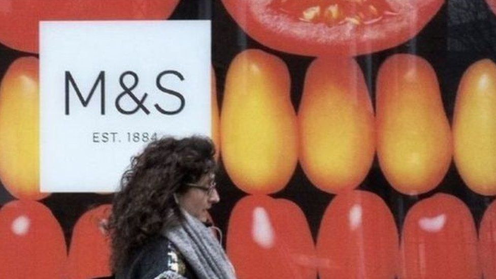 Woman walks by M&S storefront