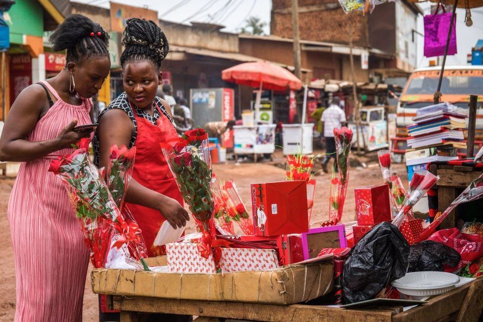 Two women chat as they look at flowers and gifts at a stall in Kampala, Uganda - Saturday 13 February 2021