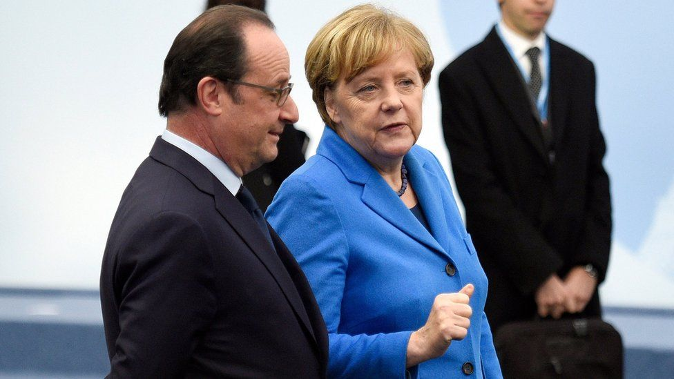 French president Francois Hollande, left, and German Chancellor Angela Merkel arrive for a group photo during the COP21, United Nations Climate Change Conference, in Le Bourget, outside Paris, Monday, Nov. 30, 2015