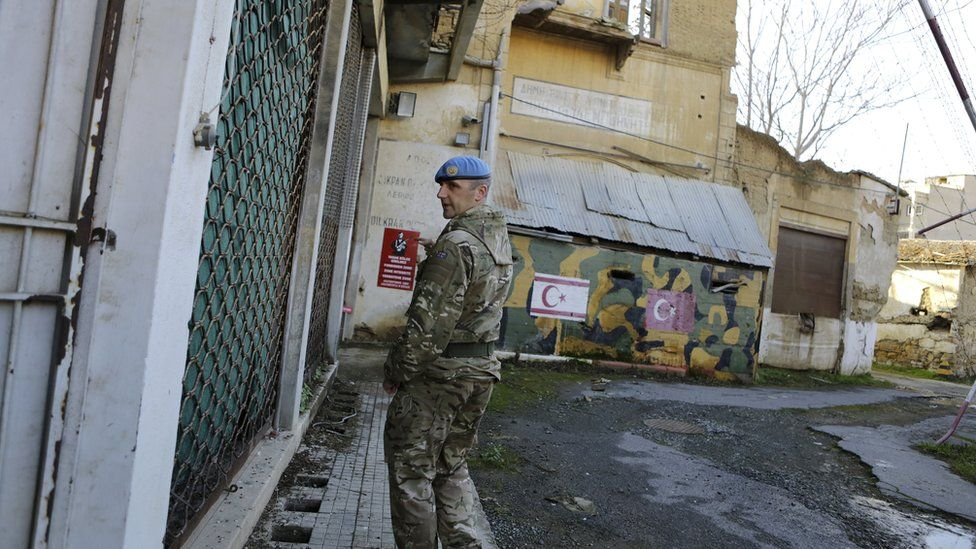 a UN soldier walks by an abandoned Turkish military guard post inside the UN buffer zone, Green Line