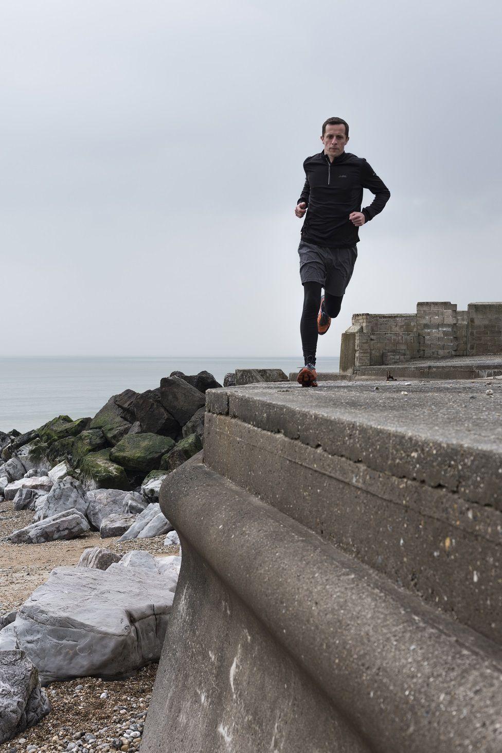Photo of Paul Shepherd running atop the sea wall