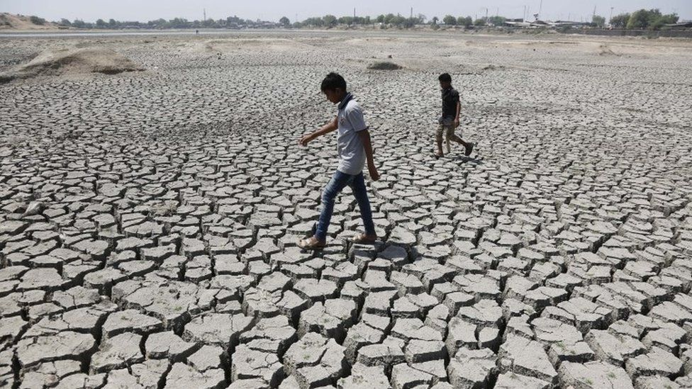 Indian boys on their way to play cricket walk through a dried patch of Chandola Lake in Ahmadabad, India, Saturday, May 14, 2016. M