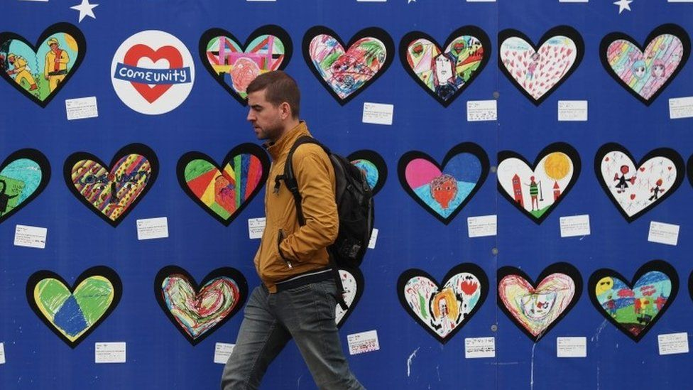 A man walks past an artwork for the victims of the Grenfell Tower fire