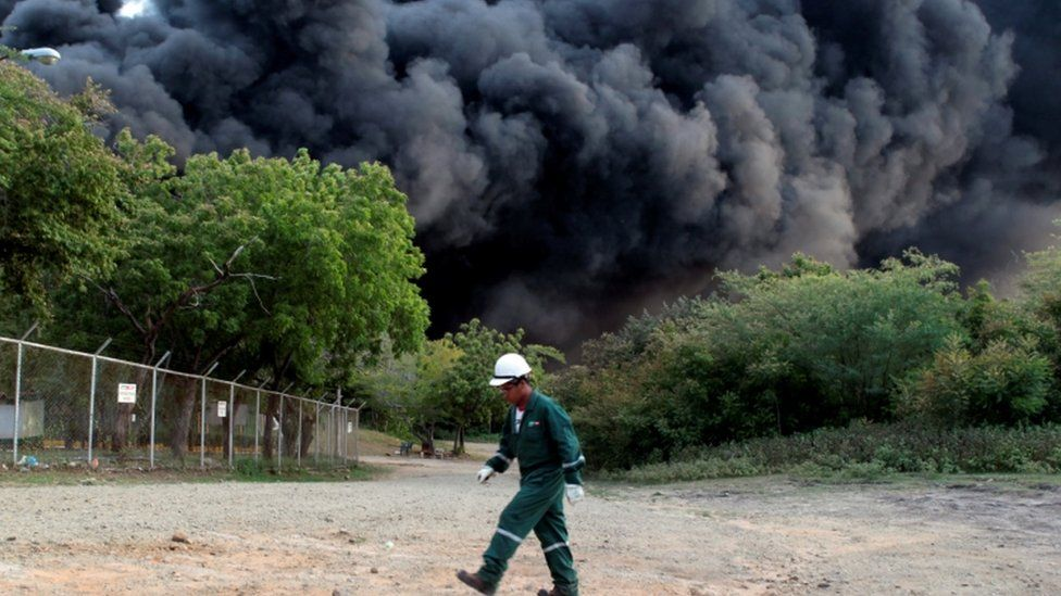 A man walks near an explosion caused by a fire at a fuel storage tank belonging to the Puma Energy company in Puerto Sandino Nicaragua 2016.