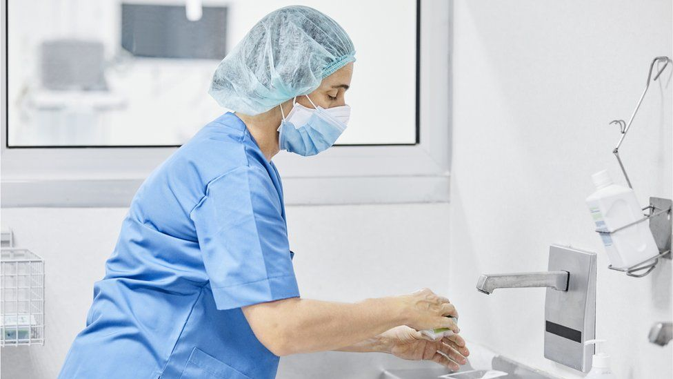 female doctor washing hands with soap at hospital.