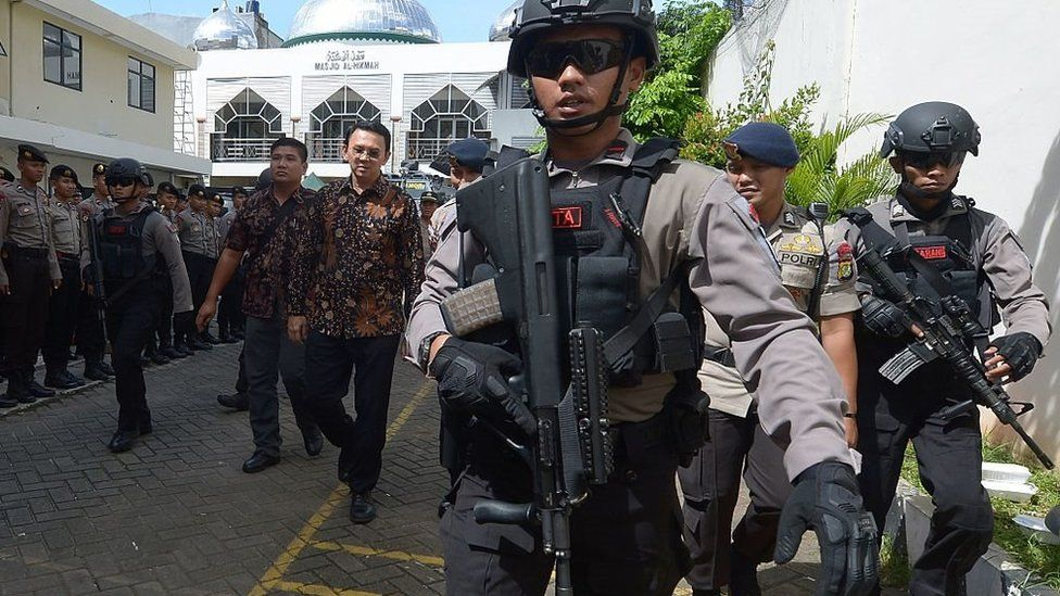 Governor Purnama (third left, in a batik shirt) being escorted by anti-terror police from the North Jakarta court in Jakarta on December 20, 2016.