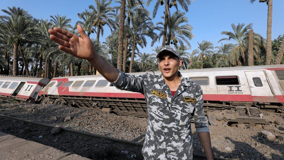 A police officer in front of a passenger train which derailed in al-Badrasheen, Egypt - Friday 13 July 2018