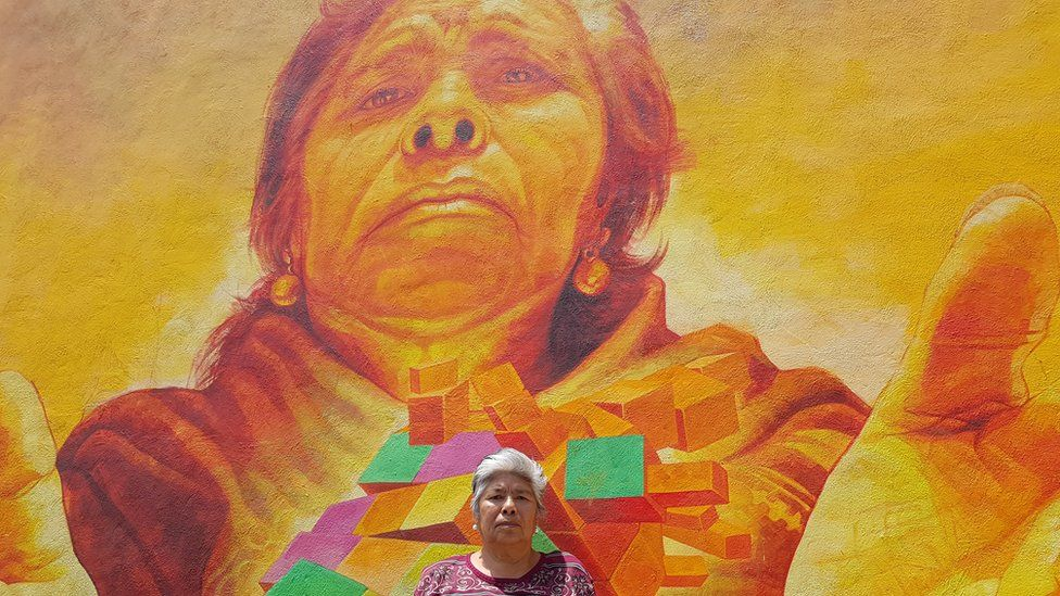 A local resident poses in front of the mural depicting her