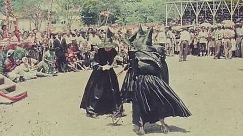 Three women dressed up as witches dance in this photograph from the 1958 Carnival in Antigua