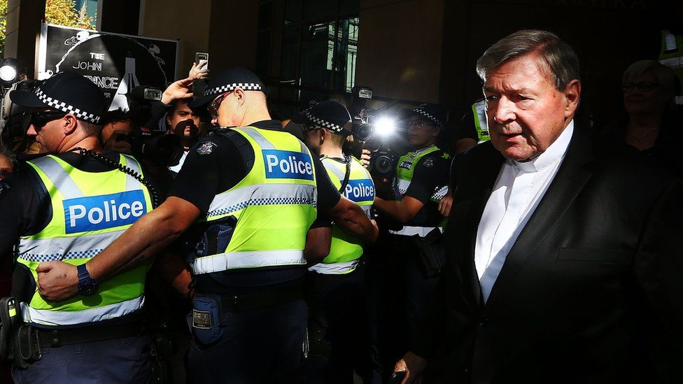 A line of police hold back media and spectators to allow George Pell to leave the Melbourne Magistrate's Court in May