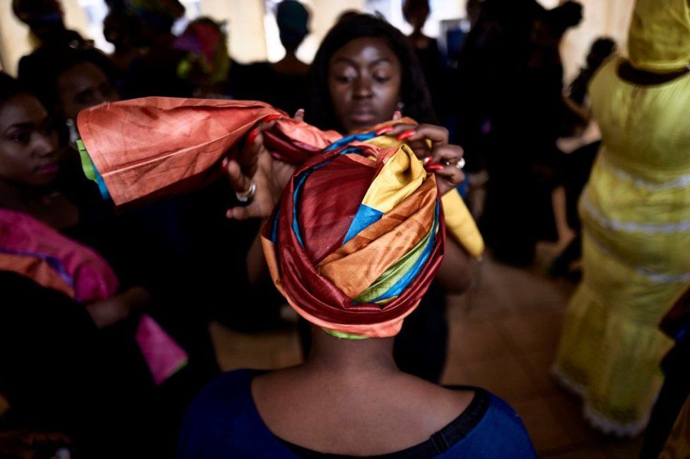 A woman ties and fastens another woman's headwrap at an event in Mali - Friday 12 February 2021