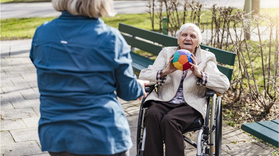 Care home resident throwing ball outdoors
