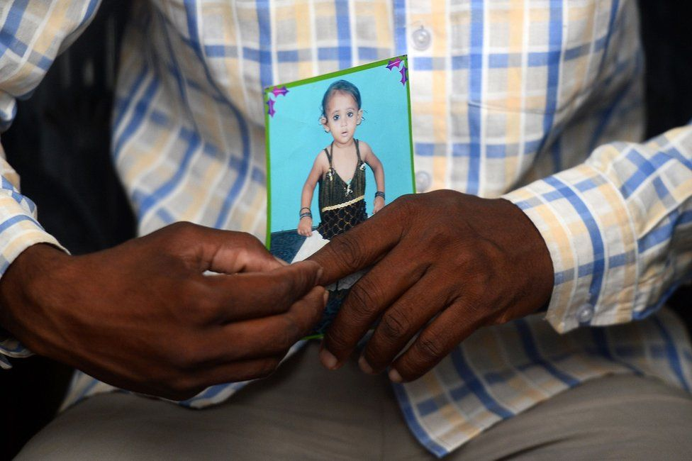 Mohamed Zahid hold a photo of his five-year-old dauhter, Khushi, in a black dress