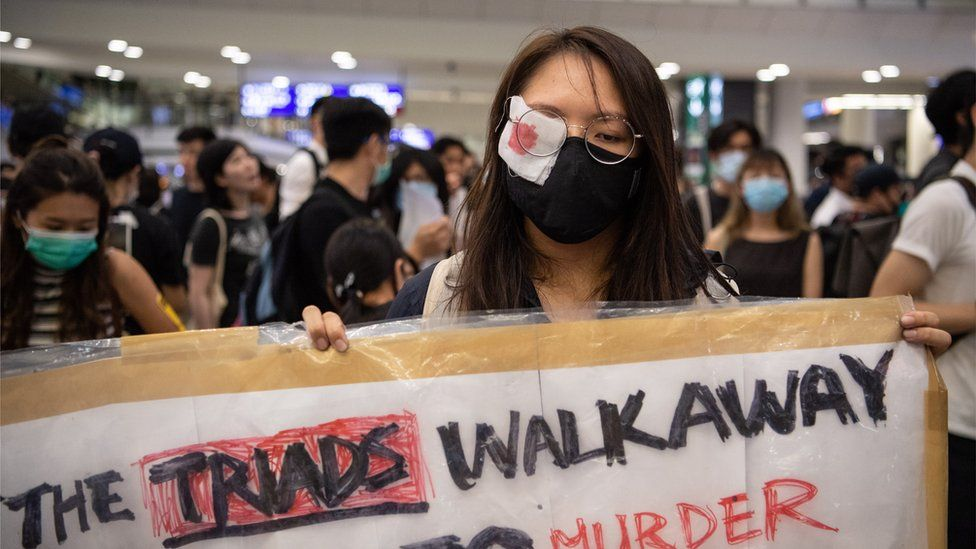 A woman wears an eye patch to protest police violence during a sit-in at Hong Kong Chek Lap Kok International Airport, Hong Kong