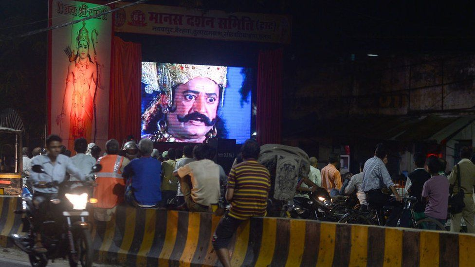 People sit along the road side watching an Indian epic television series of Ramayana, the story of the battle of Hindu god Rama over the demon king Ravana, as they celebrate Navratri (Nine Nights) culminating on the tenth night with the Dusshhra festival depicting the victory of Good over Evil, in Allahabad on September 25, 2017