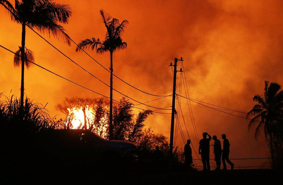 """Lava erupts from a Kilauea volcano fissure as people gather on a residential street in Leilani Gardens, on Hawaii""""s Big Island, on May 23, 2018 in Pahoa, Hawaii"""