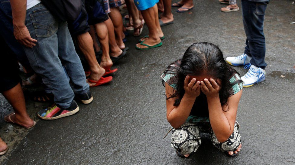 A family friend weeps after Nora Acielo, 47, was gunned down by unidentified men while escorting her two children to school in Manila, Philippines December 8, 2016