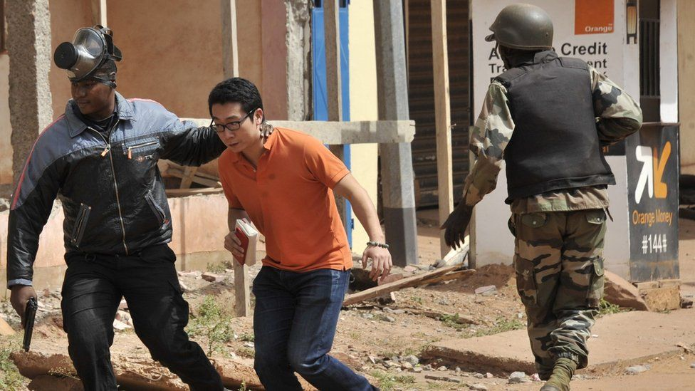 Malian security forces evacuate a man from the hotel