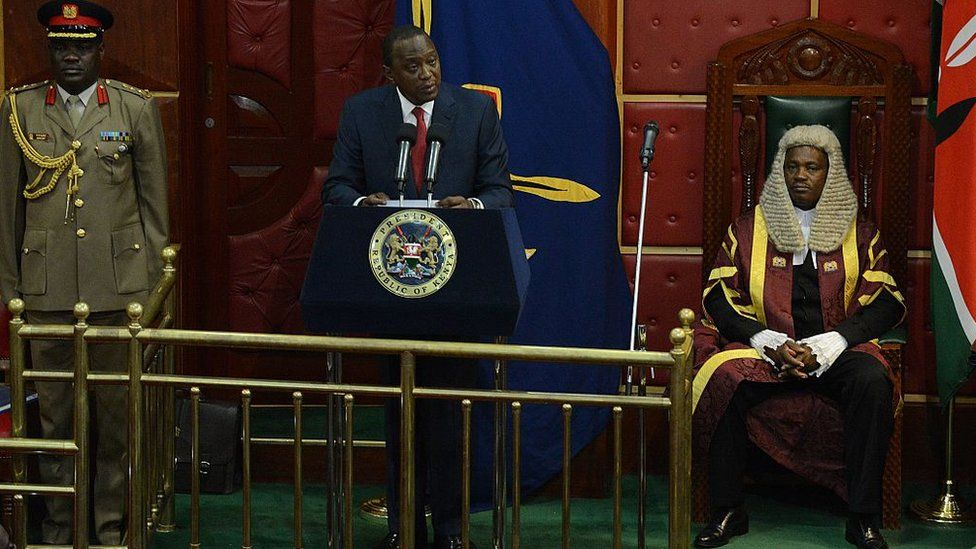 President Uhuru Kenyatta (C) flanked by speaker of the National Assembly Justin Muturi (R) addresses the parliament on March 26, 2015 in Nairobi