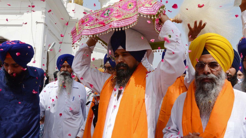 Indian Sikh priest Balwinder Singh (L) escorts the Sikh Holy Book the Guru Granth Sahib during a procession from the Gurudwara Shaheed Baba Deep Singh temple to the Gurudwara Lohgarh Sahib temple in Amritsar on June 12, 2015