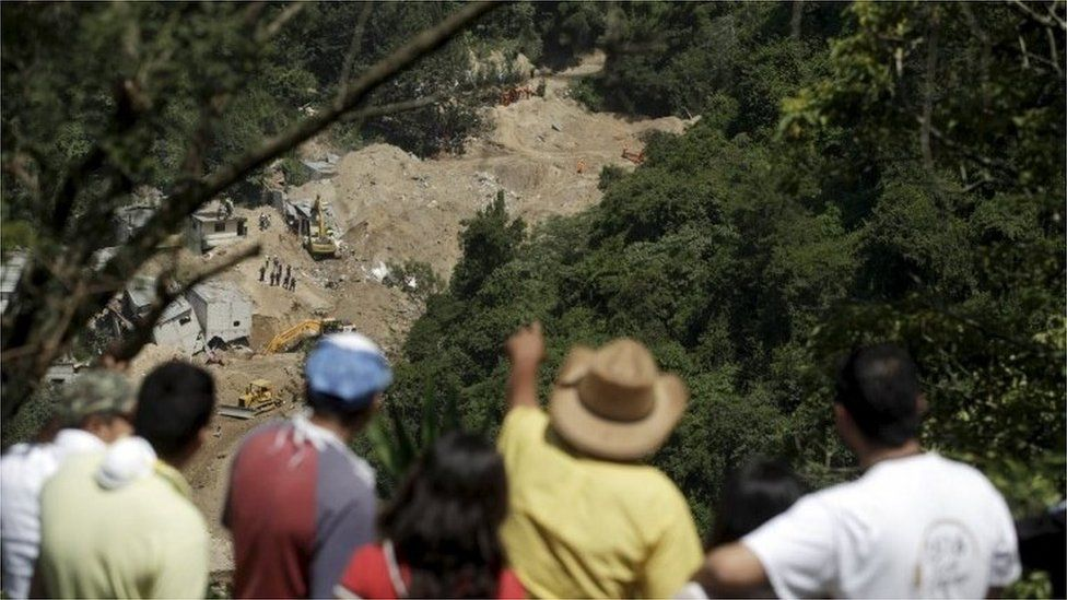 People watch an area affected by a mudslide in Santa Catarina Pinula on 7 October, 2015