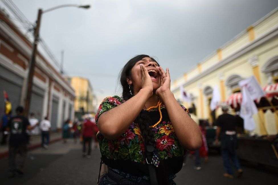 A woman yells slogans during a protest march in Guatemala City