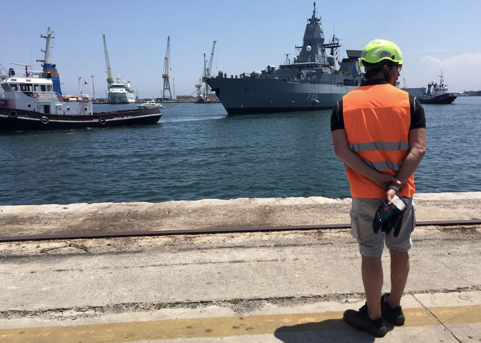 An Italian official waiting on the docks for a European military ship that has been conducting search and rescue in the Mediterranean