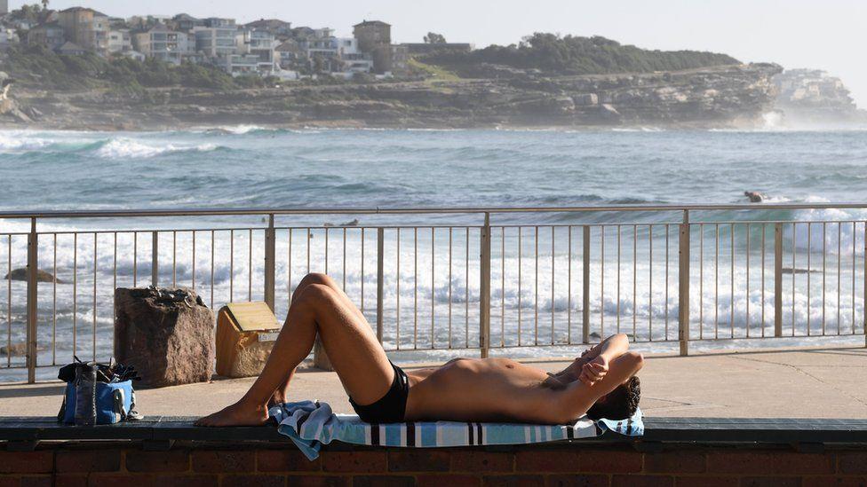 A man sunbakes at a Sydney beach