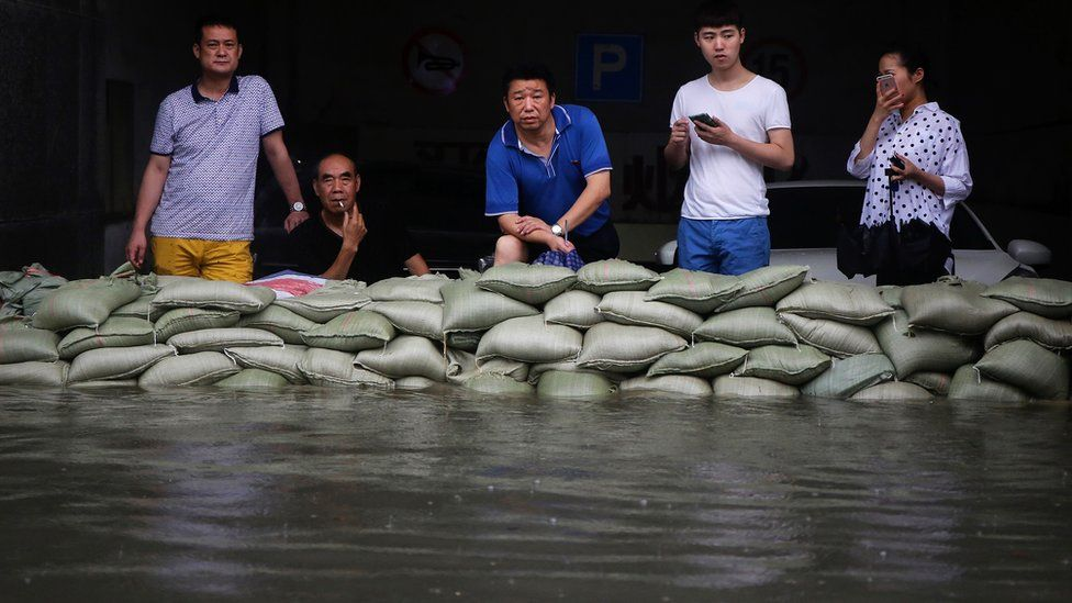 People stand behind sandbags holding back water