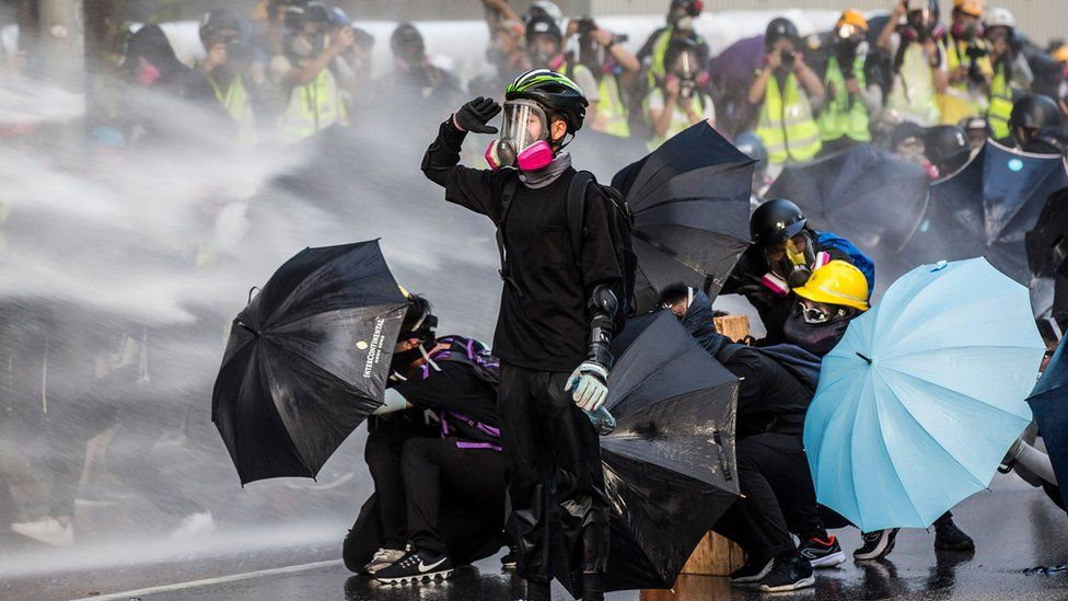Pro-democracy protesters react as police fire water cannons outside the government headquarters in Hong Kong on 15 September 2019
