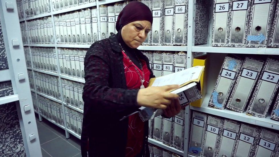 one of the researchers at the commission looks at files in its library