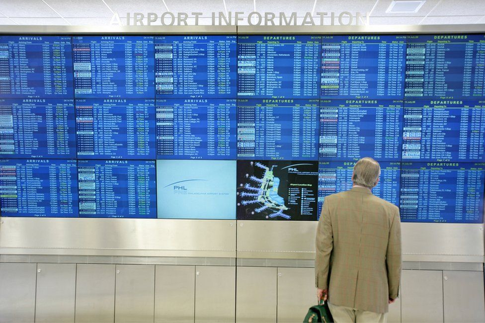 A person stands in front of a collection of airport information screens displaying arrivals and departures