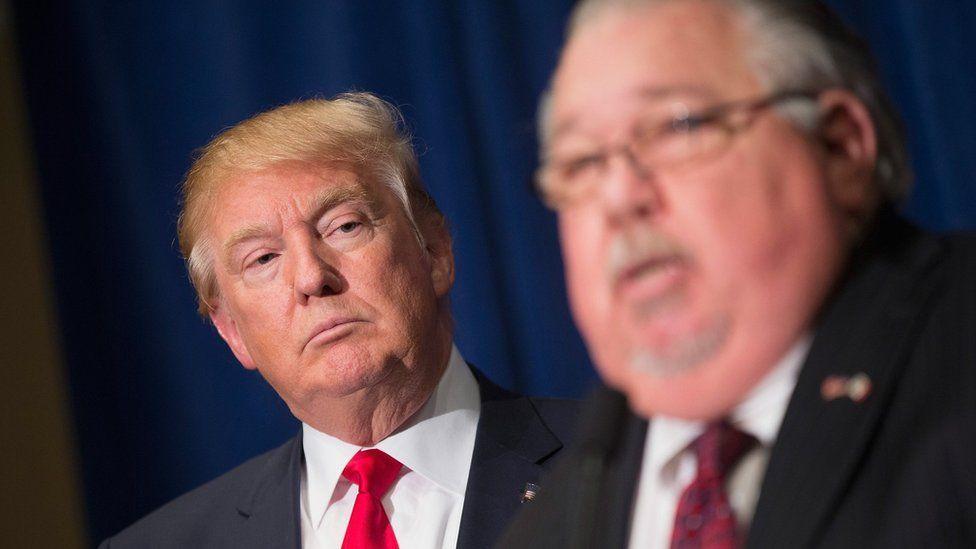 Republican presidential candidate Donald Trump (L) listens as Sam Clovis speaks in Dubuque, Iowa, on 25 August 2015