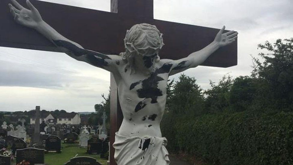 A damaged statue of Christ on a crucifix