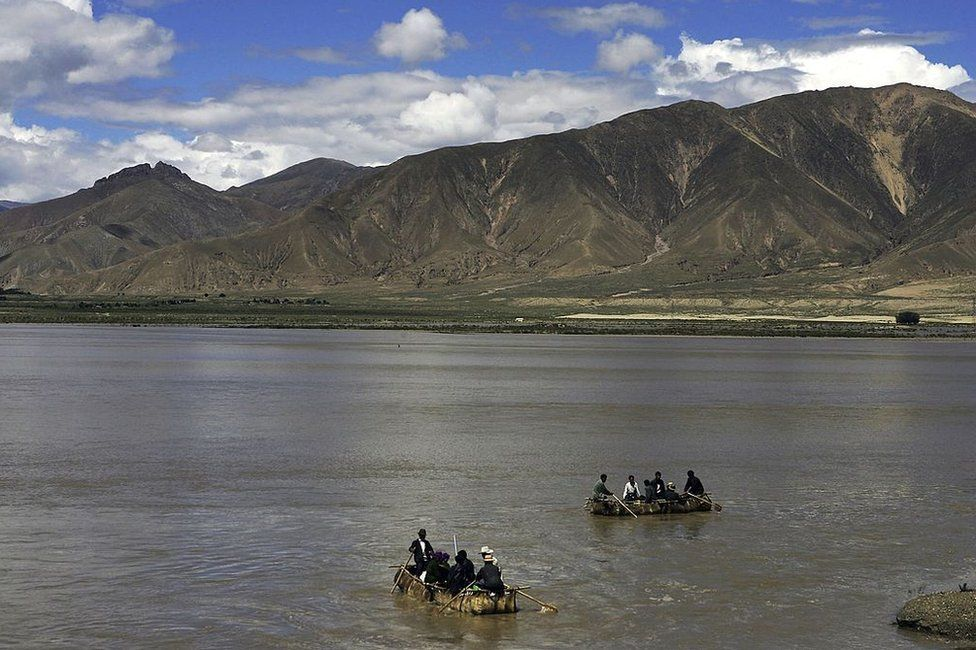 Tibetan people row cowskin rafts on the Brahmaputra River on August 30, 2006 in Renbu County of Tibet Autonomous Region, China. Cowskin is a traditional material used to make rafts for fishing and to cross rivers and lakes for the Tibetan people.