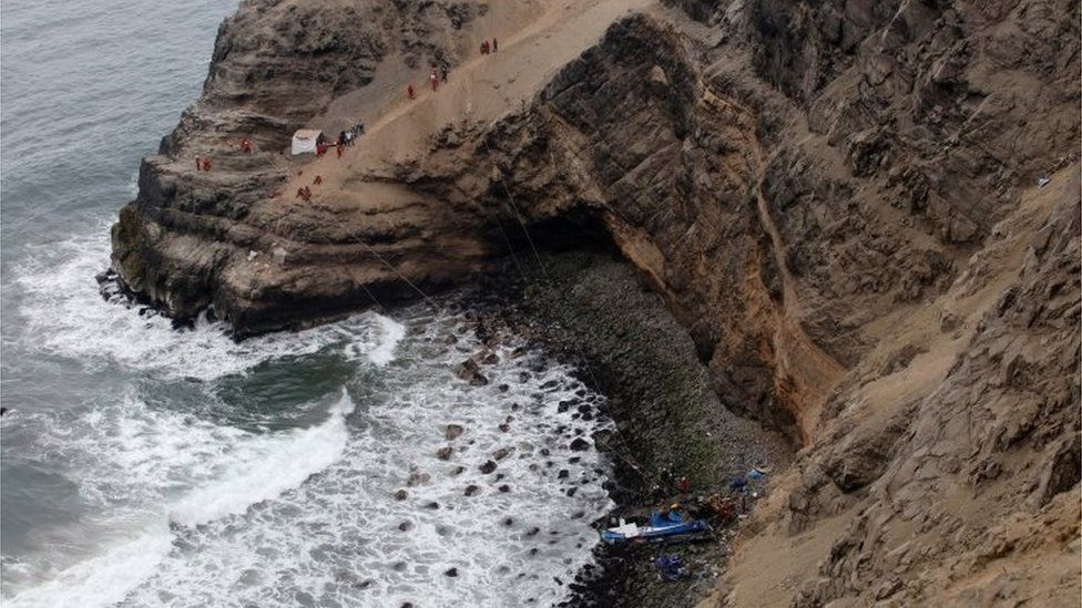 Rescue workers work at the scene after a bus crashed with a truck and careened off a cliff along a sharply curving highway north of Lima, Peru, January 3, 2018.