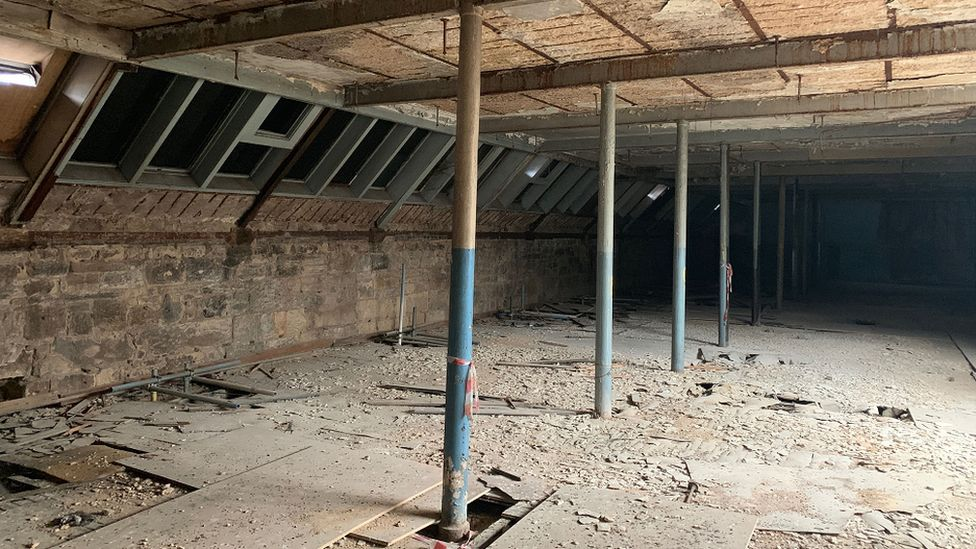 A shot of the interior. The floor is dirty with supporting columns for the roof
