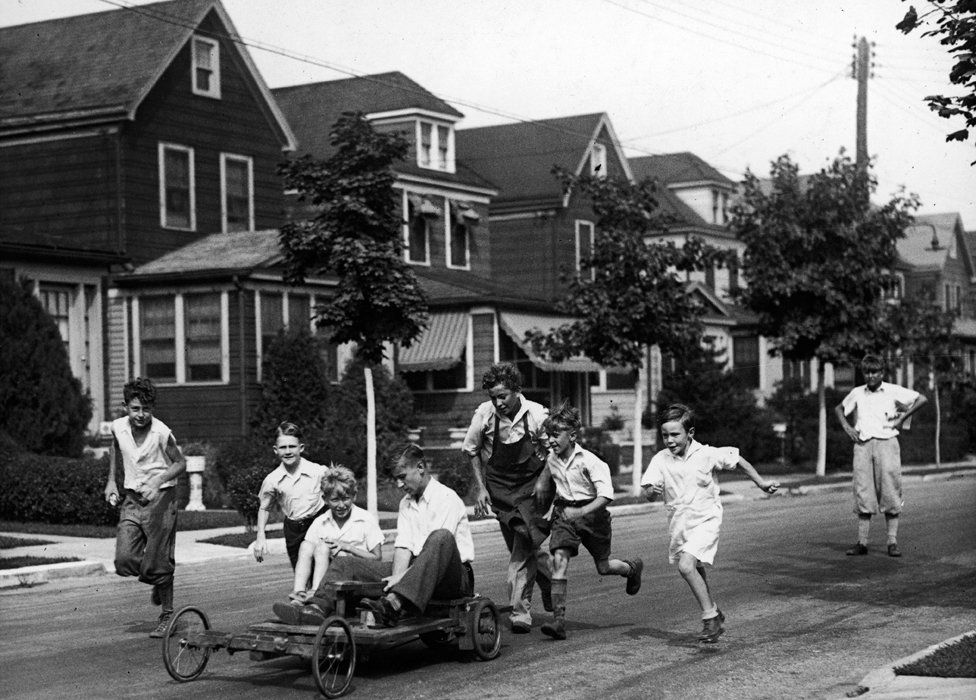 A group of boys on a residential street run after the go-kart that they have put together from an old motorcycle and a homemade chassis, 1930s.
