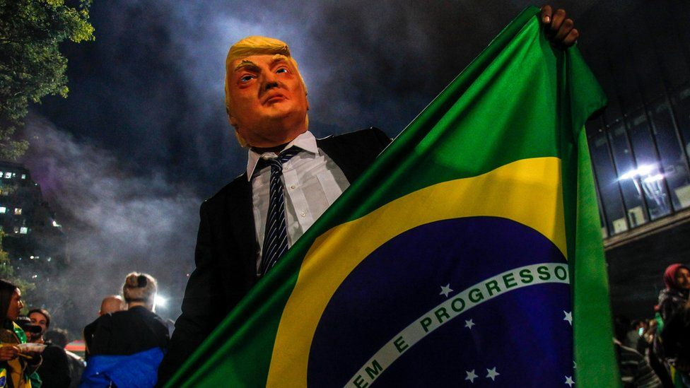 A supporter of Mr Bolsonaro wears a mask of US President Donald Trump