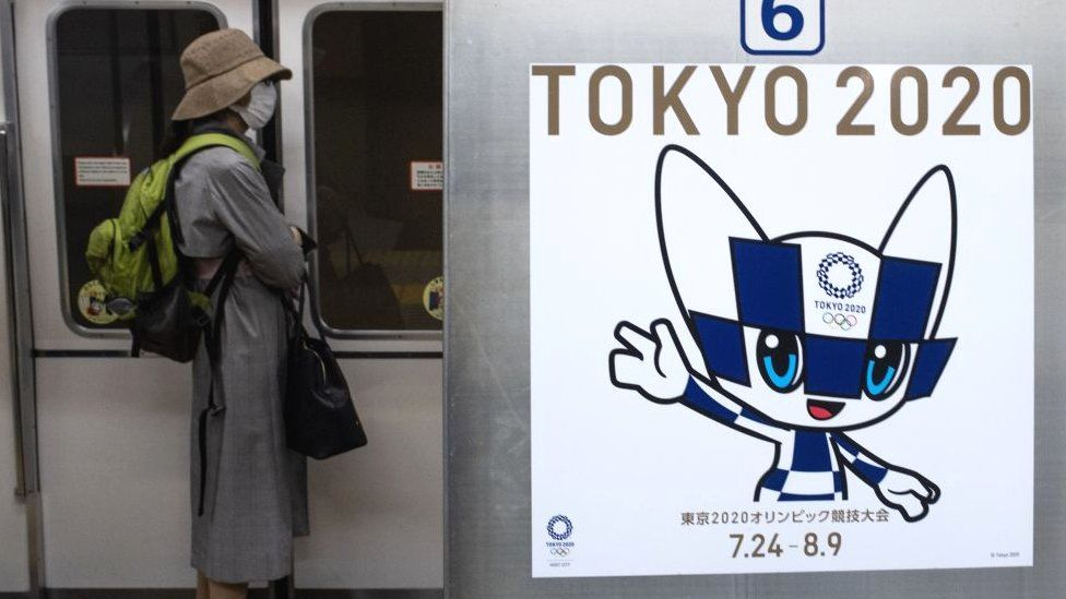 A passenger wearing a face mask stands next to a poster of Tokyo 2020 Olympic mascot Miraitowa on a train in Tokyo on April 20, 2020.