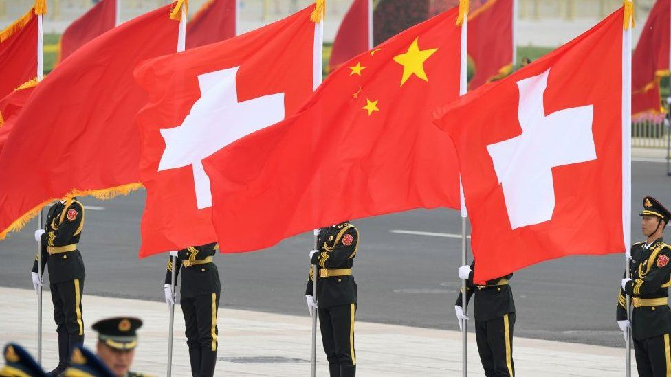 Chinese honour guards stand with Swiss and Chinese flags