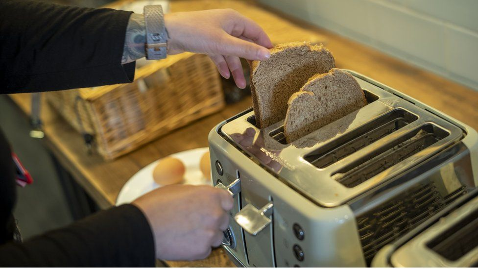 A woman places some bread in a toaster