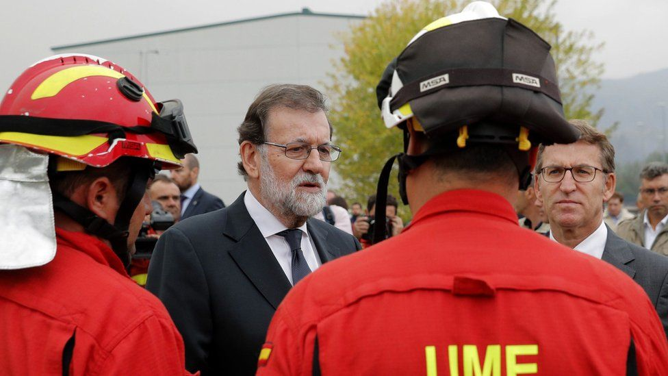 Spanish Prime Minister Mariano Rajoy (2nd left) and Galicia region leader Alberto Nunez Feijoo meet emergency workers during a visit to an area hit by fire Pontevedra,