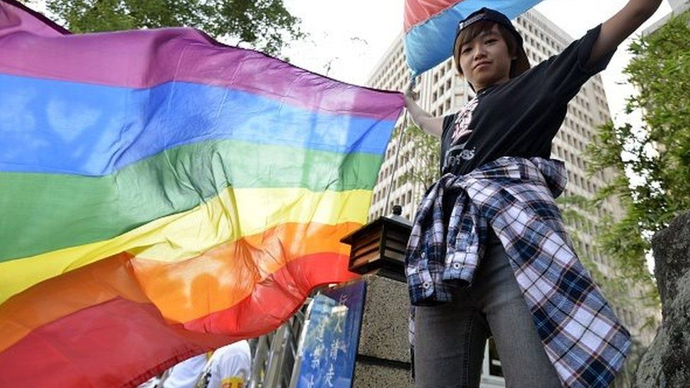 Ảnh chụp ngày 17/11/2016 một người ủng hộ hôn nhân đồng tính cầm cờ mầu cầu vồng biểu tượng những người đồng tính và chuyển giới bên ngoài tòa nhà Quốc hội ở Đài Bắc.