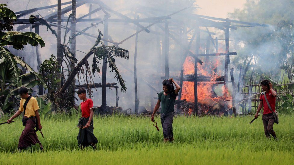 Armed men walk past burning homes in Rakhine state