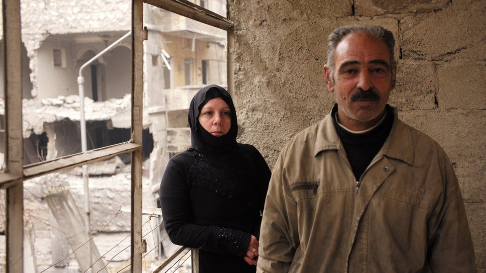Abu Hussein and Umm Hussein stand next to blown out windows